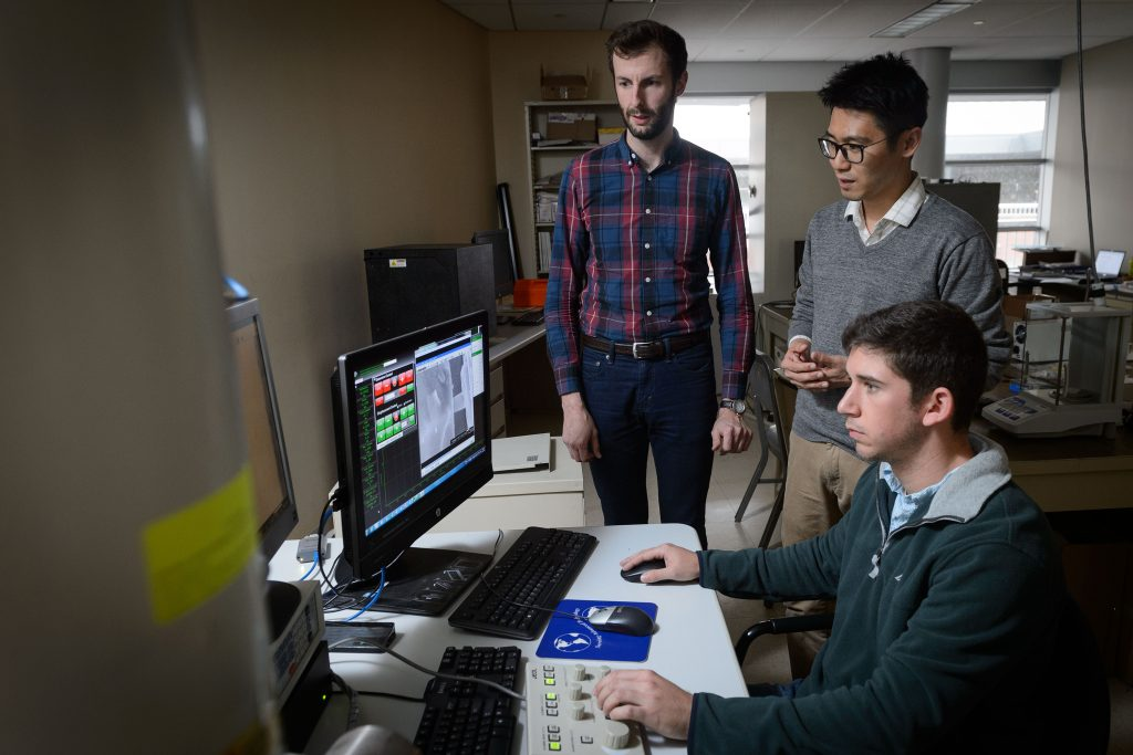 Seok-Woo Lee, assistant professor of materials science and engineering, center, with graduate students Keith Dusoe, left, and John Sypek at the controls of a scanning electron microscope at their lab at the Gant Complex on Oct. 27, 2016. (Peter Morenus/UConn Photo)