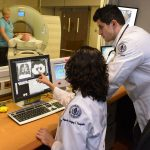 Dr. Omar Ibrahim, right, director of thoracic oncology at the Carole and Ray Neag Comprehensive Cancer Center, UConn Health, and Dr. Electra Kaloudis, section head of thoracic imaging in the Department of Diagnostic Imaging and Therapeutics, look over a low dose CT scan. (Janine Gelineau/UConn Health Photo)