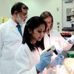 Pramod Srivastava (left), director of the Carole and Ray Neag Comprehensive Cancer Center at UConn Health, oversees students Nandini Acharya (foreground) and Stephanie Floyd in his lab. (Carolyn Pennington/UConn Health Photo)