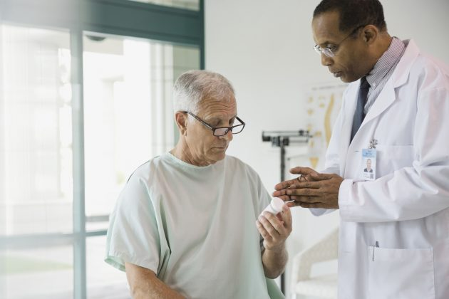 A doctor discusses a prescription medication with a senior patient. (Getty Images)