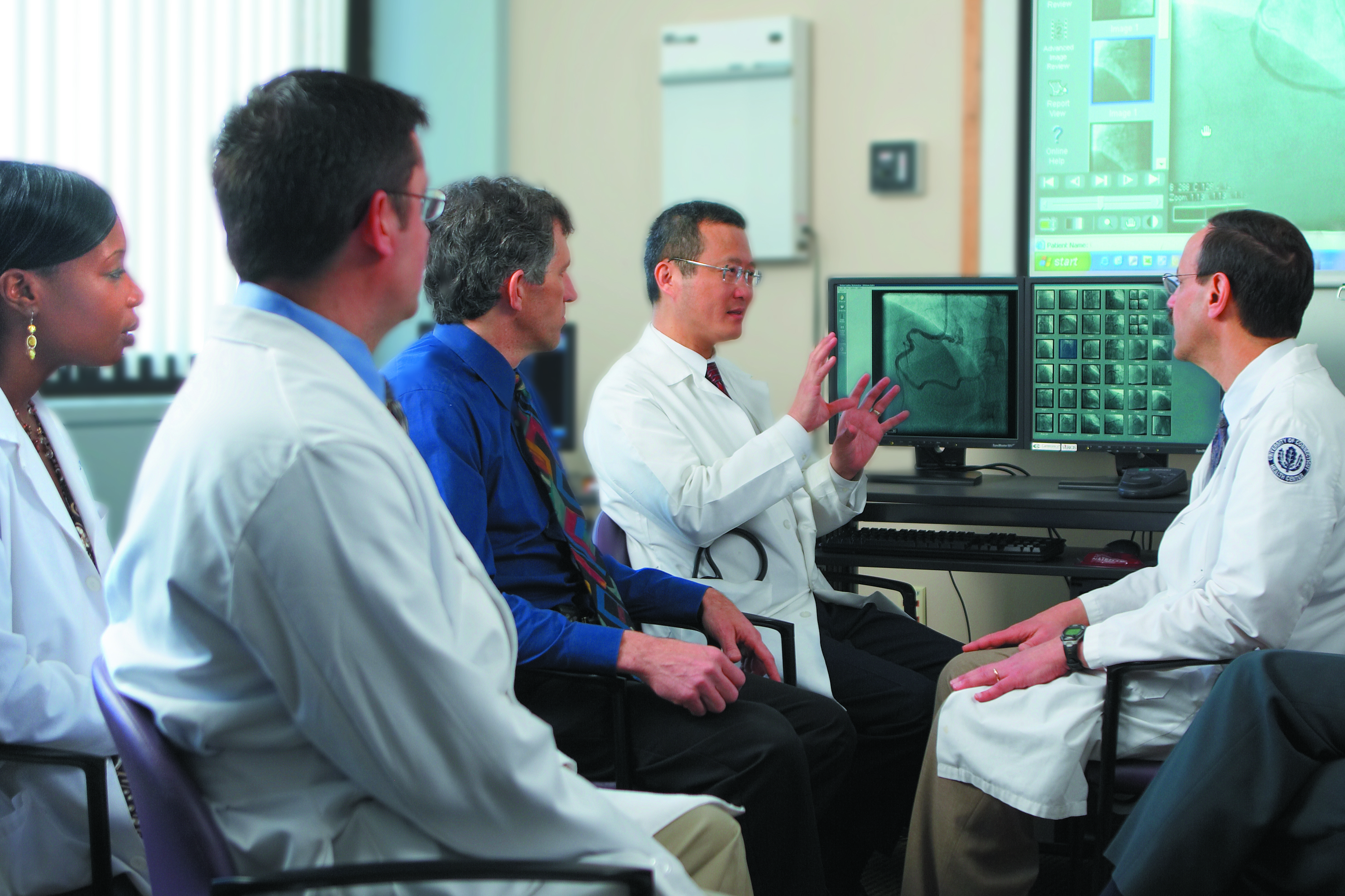 Dr. Bruce Liang, center, reviews a patient's case with physicians from the Pat and Jim Calhoun Cardiology Center. (Lanny Nagler for UConn Health Center)