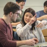 Undergraduates Richard Vincent III, left, and Cindy Lin discuss a hands-on exercise called 'Design Thinking: Marshmallow Challenge' during a class on incorporating game design into business planning. (Sean Flynn/UConn Photo)