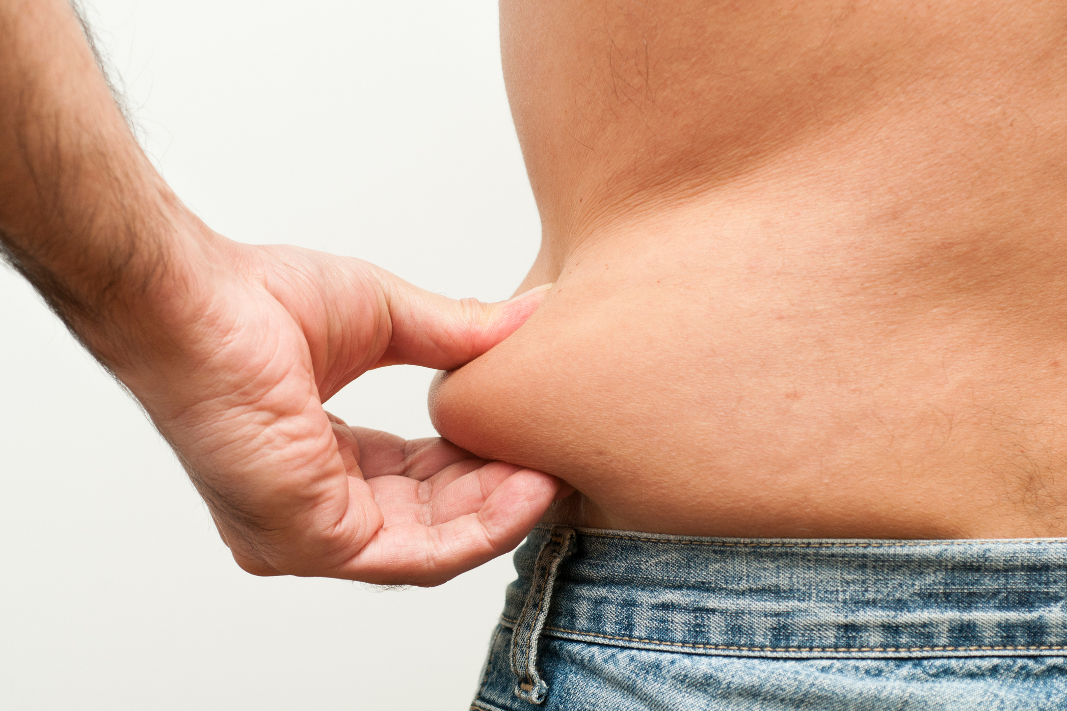Close up shot of a man pinching fat from his belly. (Getty Images)
