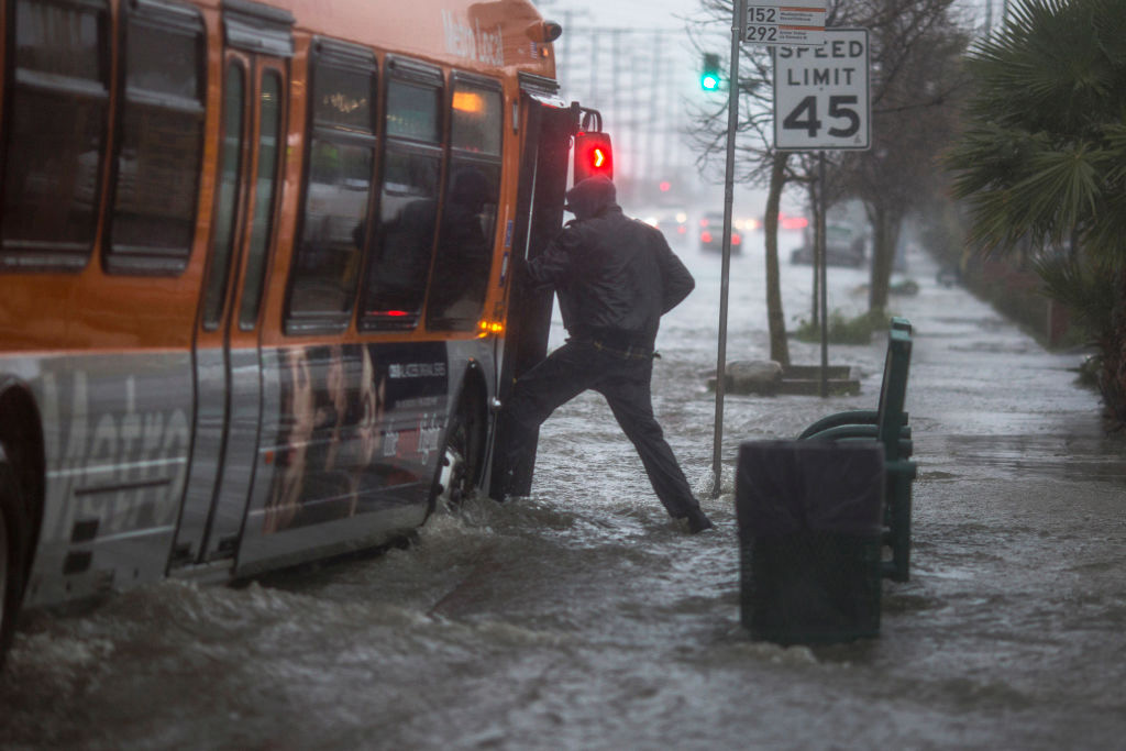 A man boards a bus on a flooded street as a powerful storm moves across Southern California on Feb. 17, 2017 near Sun Valley, Calif. After years of severe drought, heavy winter rains came to the state, and with them, the issuance of flash flood watches in three counties, and the evacuation of hundreds of residents from Duarte, Calif. for fear of flash flooding from areas denuded by a wildfire last year. (Photo by David McNew/Getty Images)