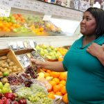 An overweight woman buying fruit at a grocery store. (UConn Rudd Center Photo)
