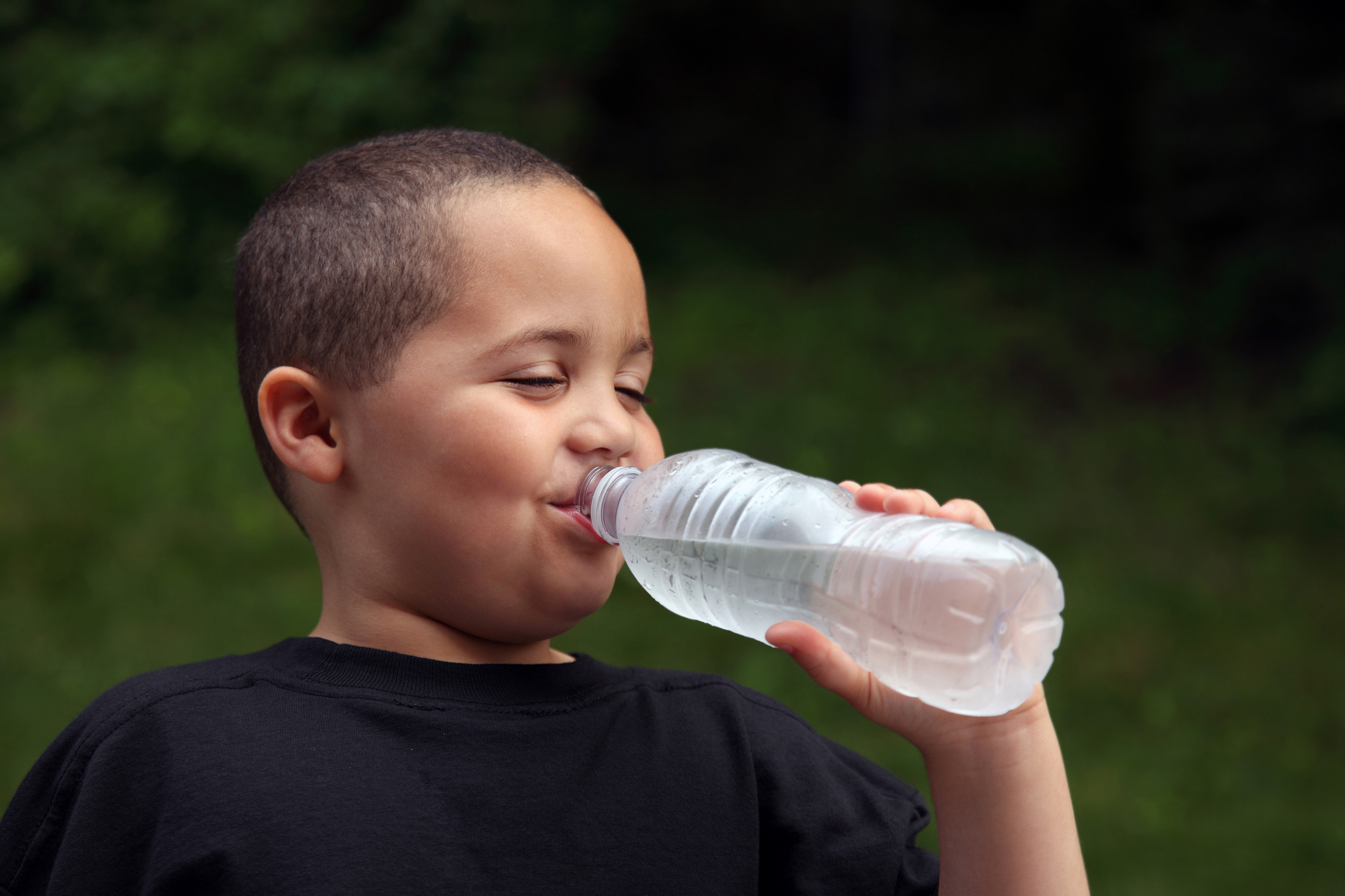 Latino boy drinking water from bottle. (Thinkstock Photo)