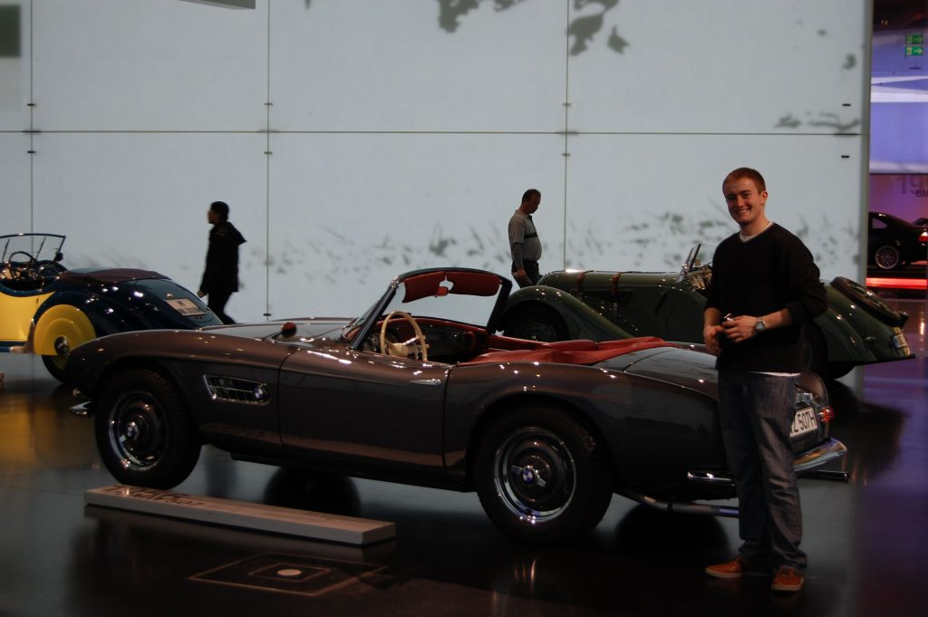 Karl Music, a graduate of the Eurotech program who currently works at Boehringer Ingelheim in Ridgefield, Connecticut, poses next to a car at the BMW Museum in Munich.