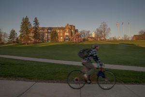A student riding his bicycle to class along Route 195. (Sean Flynn/UConn Photo)