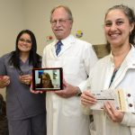 UConn Health's Myra Rivera, Sidney Hopfer, and Giuseppa Santaniello (left to right) demonstrate tools used to screen newborns for cystic fibrosis and provide genetic counseling for parents. On the tablet is Amy Jonasson, a certified genetic counselor from University of Florida Health. (Photo by Janine Gelineau)