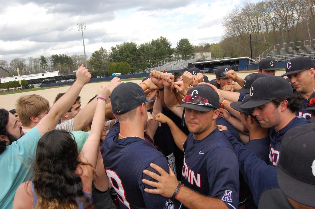 Music students who met with the baseball team as part of the Arts and Athletics program in the School of Fine Arts huddled together on the field after the Huskies' win over Cincinnati on April 30. (Kenneth Best/UConn Photo)