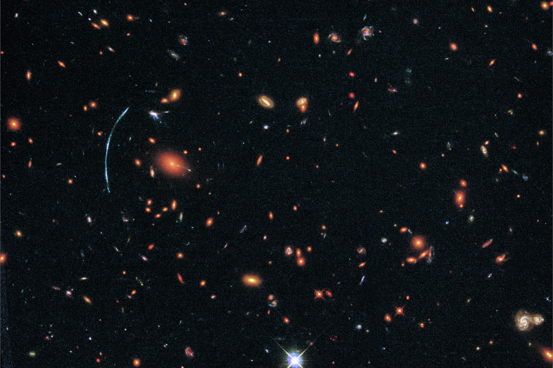 The galaxy cluster shown here, SDSS J1110+6459, was discovered as part of the Sloan Giant Arcs Survey. It is located about 6 billion light-years from Earth (redshift of z=0.659) and contains hundreds of galaxies. At left, a distinctive blue arc is actually composed of three separate images of a more distant background galaxy called SGAS J111020.0+645950.8. The background galaxy has been magnified, distorted, and multiply imaged by the gravity of the galaxy cluster in a process known as gravitational lensing. (HUBBLESITE)
