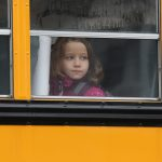 A child gazes from a school bus. (Photo by John Moore/Getty Images)