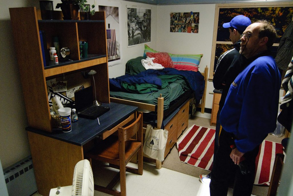 Prospective students and parents look at the Model Room - a model of what a double in a dorm looks like.