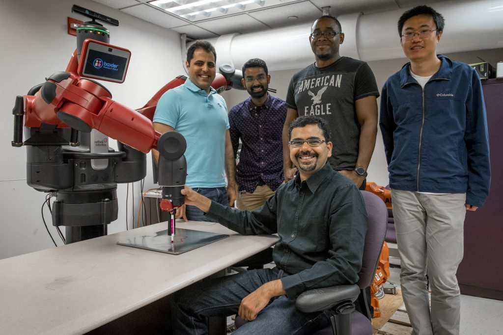 From left back row, Ph.D. students Iman Salehi, Harish Ravichandar, Kyle Hunte, Gang Yao, and seated, Ashwin Dani, assistant professor of electrical and computer engineering. (Sean Flynn/UConn Photo)